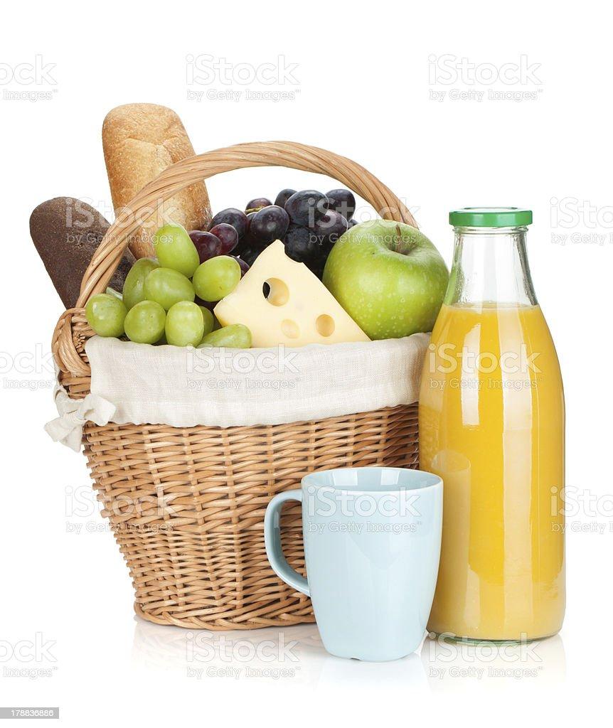 Picnic basket with bread, fruits and orange juice bottle royalty-free stock photo