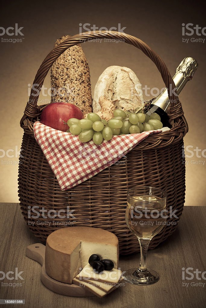 Picnic basket with bread, wine, cheese, olives and apples royalty-free stock photo