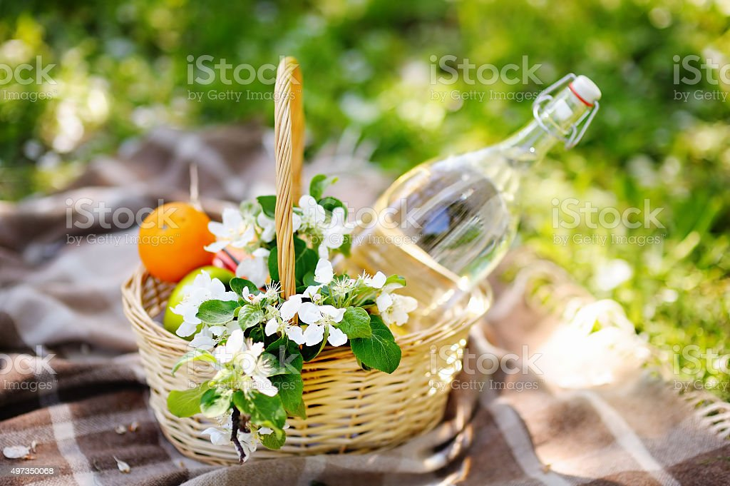 Picnic basket with fruits and flowers stock photo
