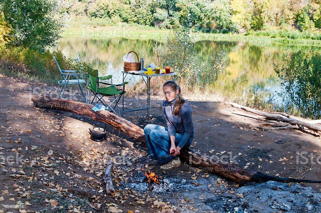 Picnic. Girl near a campfire. Autumn stock photo