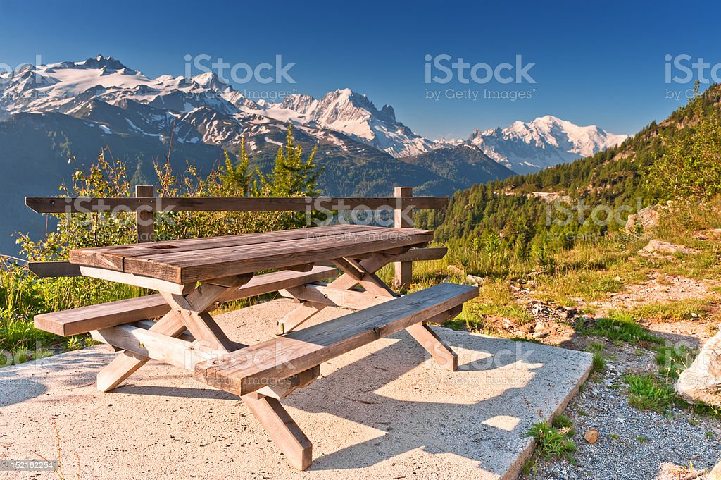 Picnic table and benches in Swiss Alps near mountain road. royalty-free stock photo