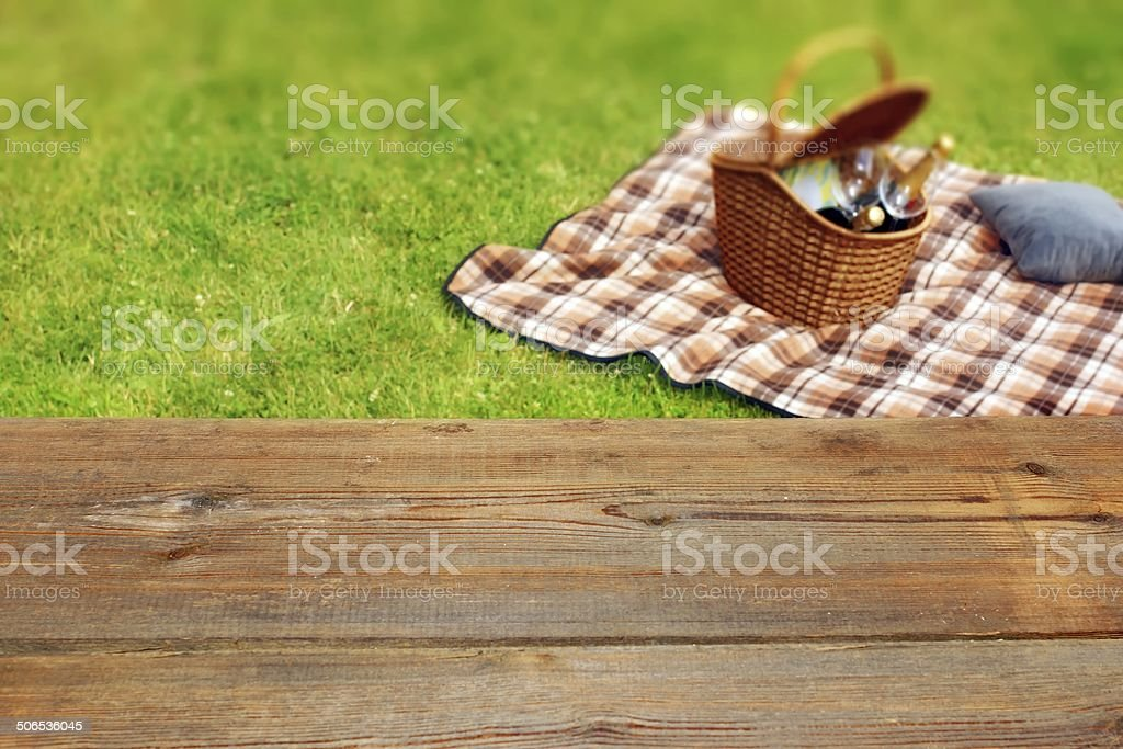 Picnic table, blanket and basket in the grass stock photo
