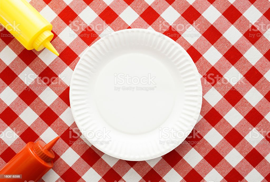 Picnic table with white plate and ketchup and mustard stock photo