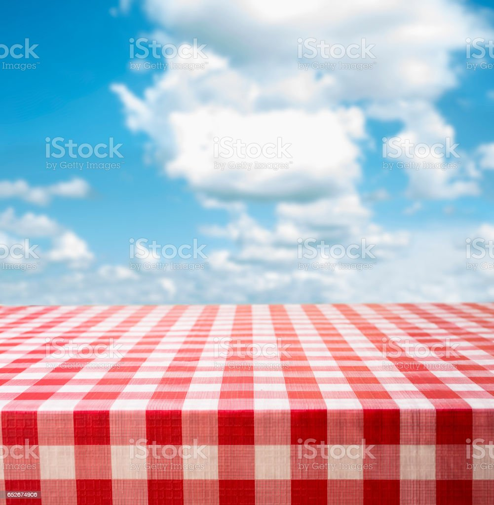 Picnic time!  Red checked tablecloth with summer cloudy blue sky. stock photo