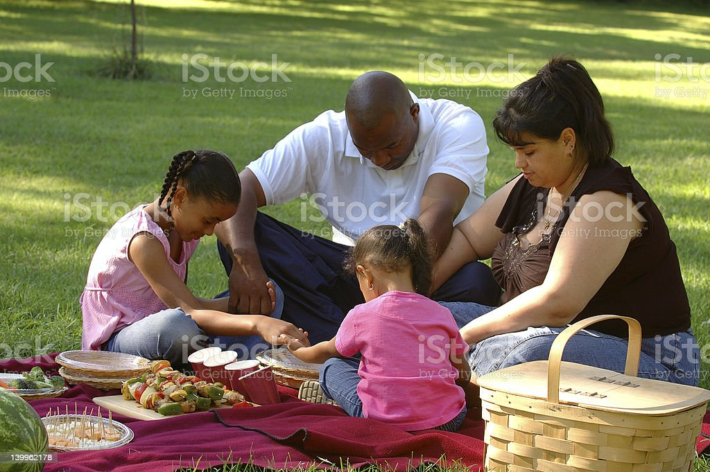 Picnicking family saying grace stock photo