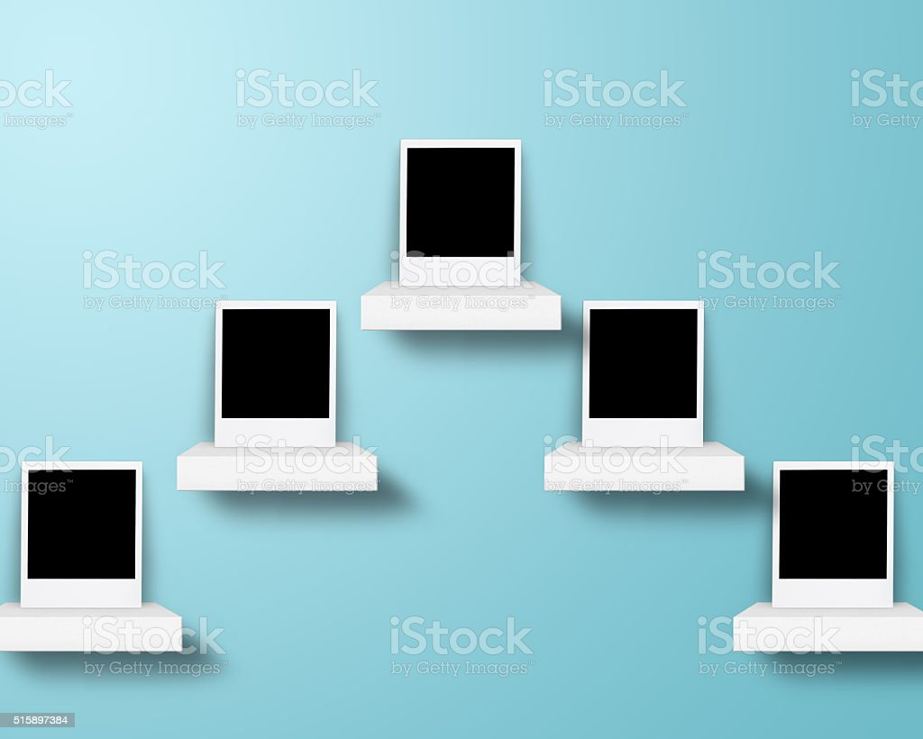 Picture frames on shelf with green wall stock photo