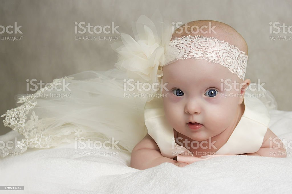 A picture of a baby taking a photo in the white dress stock photo