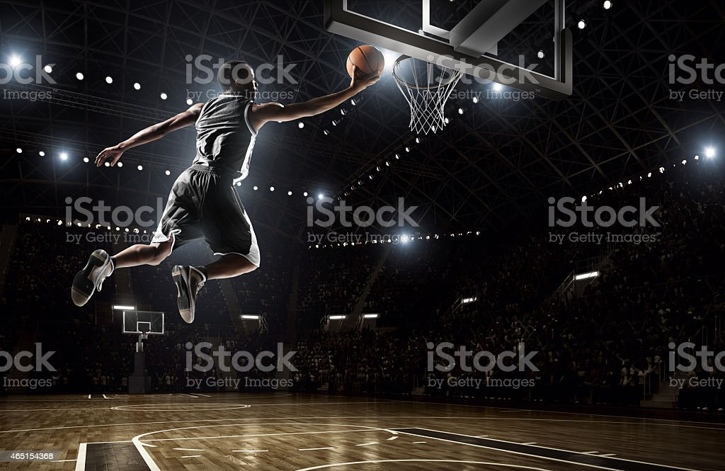 A picture of a basketball player dunking stock photo