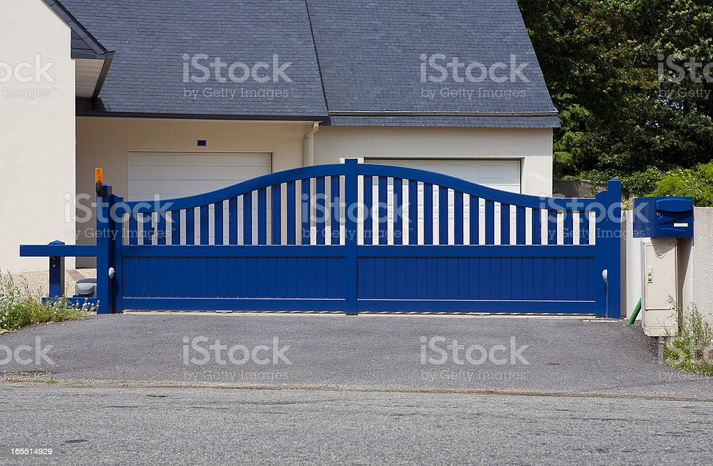 A picture of a blue gate around a house stock photo