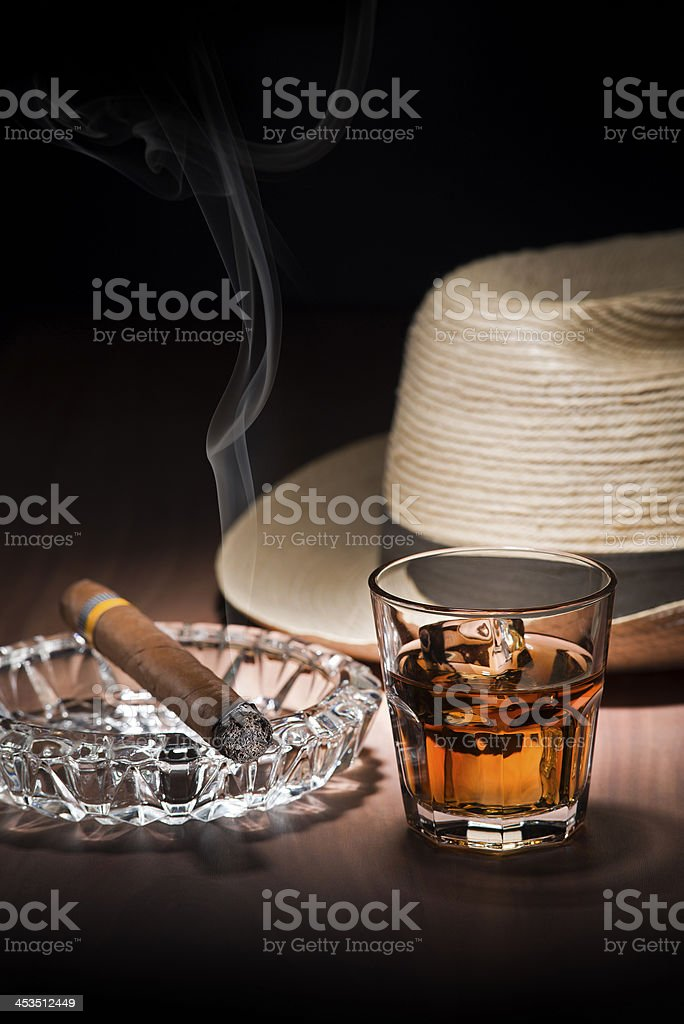 Picture of a cigar lit in an ashtray with a glass of whiskey stock photo