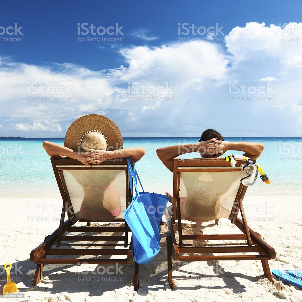 A picture of a couple sitting on the beach in chairs stock photo