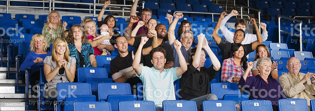 A picture of a crowd sitting in benches cheering royalty-free stock photo