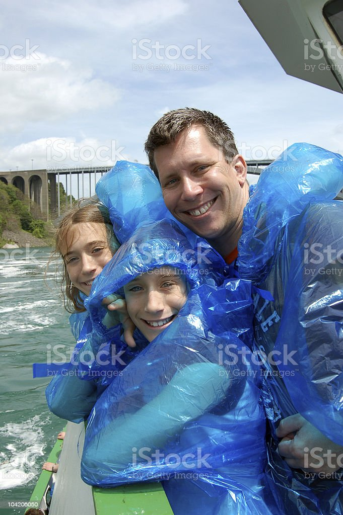 A picture of a father and his daughters on a boat stock photo