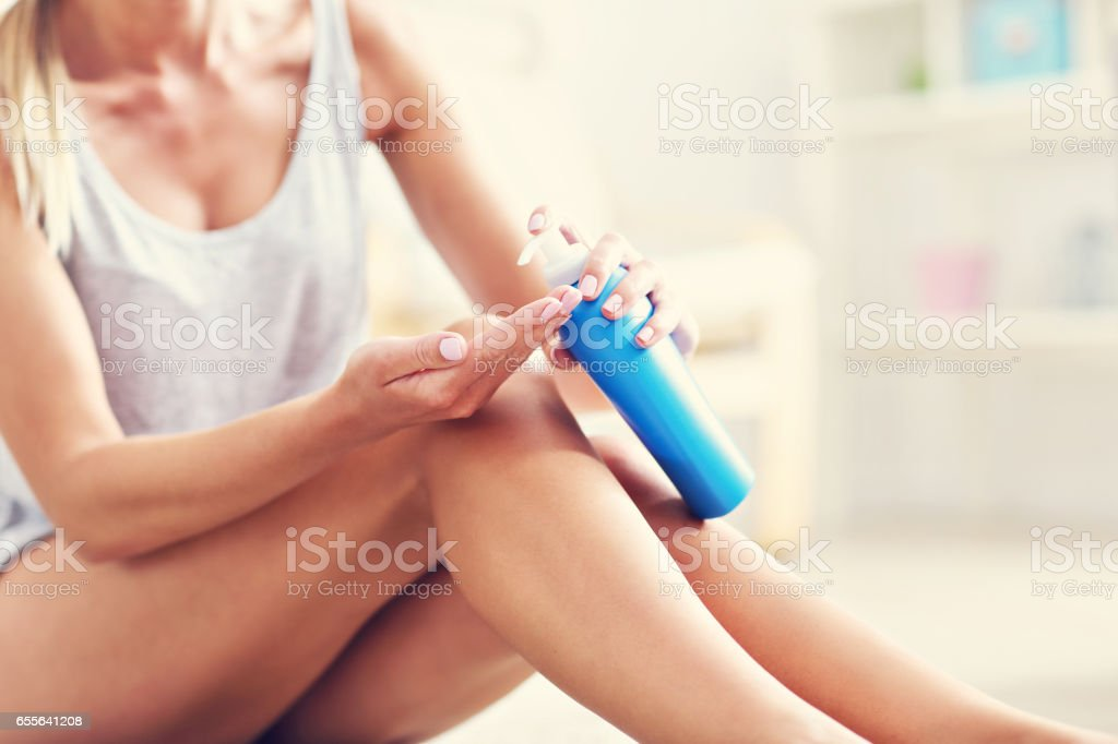 Picture of a fit woman holding lotion over her legs stock photo