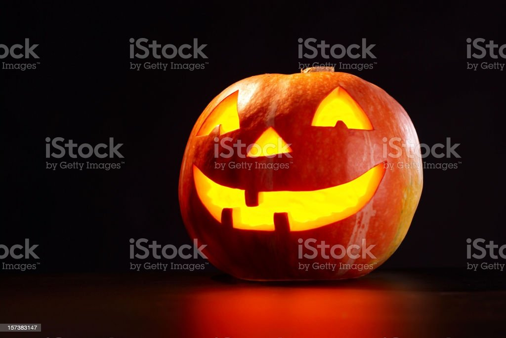 A picture of a lit pumpkin on a black background stock photo