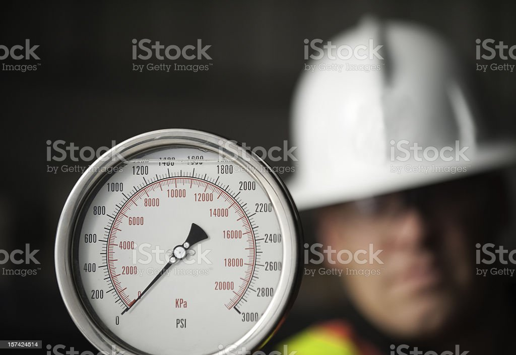 A picture of a man looking at a gauge stock photo