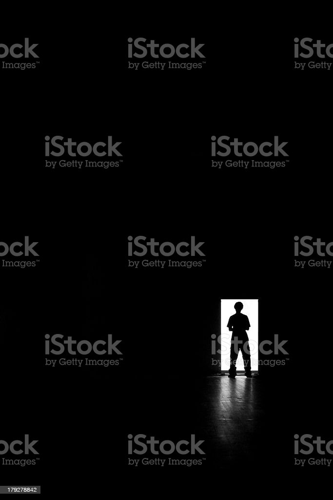 A picture of a person standing in a doorway by themselves  royalty-free stock photo