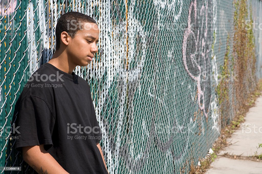 A picture of a teenager leaning on a fence royalty-free stock photo
