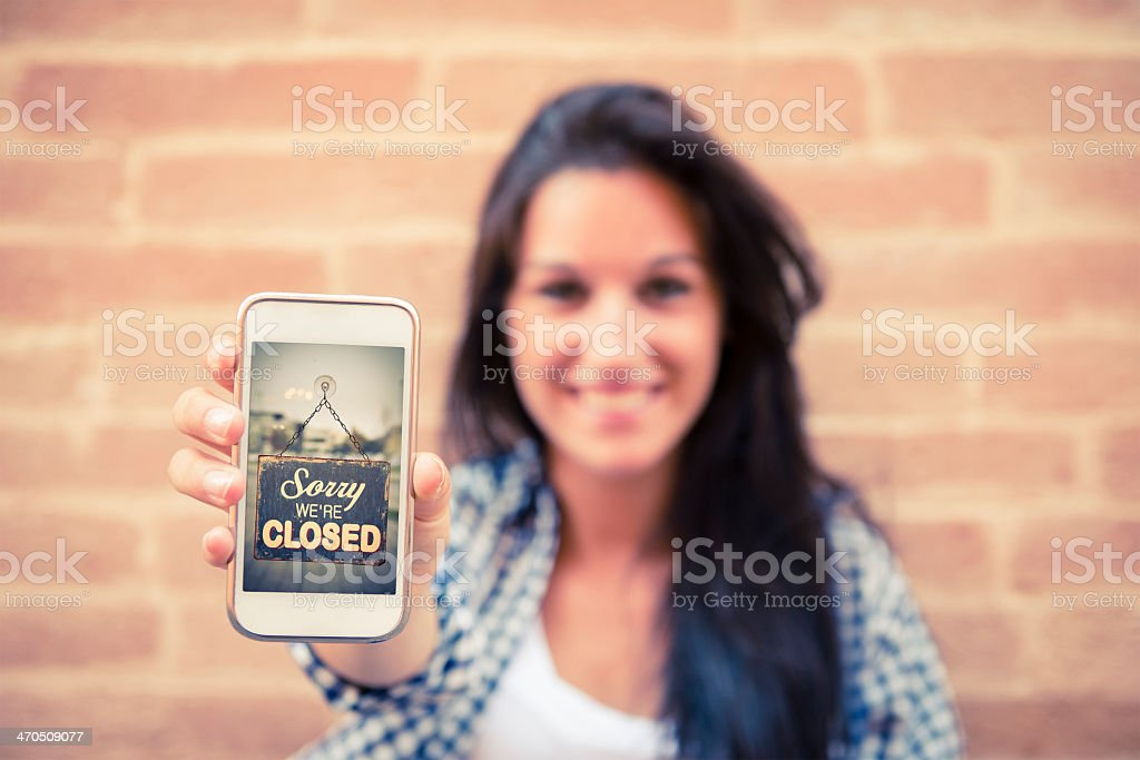 A picture of a woman holding a phone with sorry we're closed stock photo