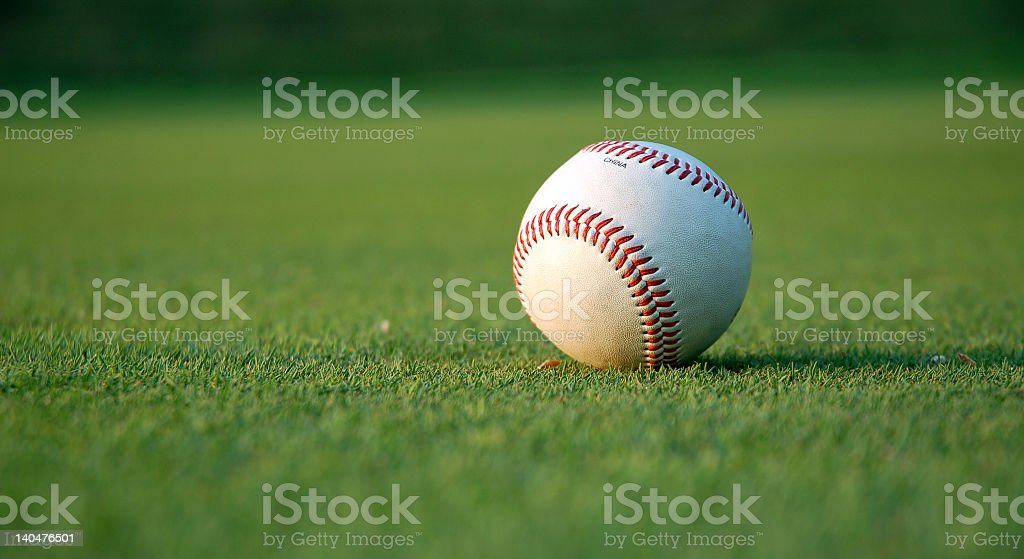 Picture of an isolated baseball on a green field stock photo