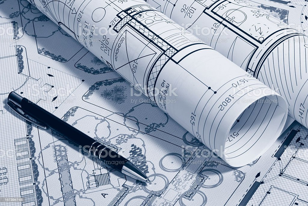 Picture of architectural plans rolled up next to a pen royalty-free stock photo
