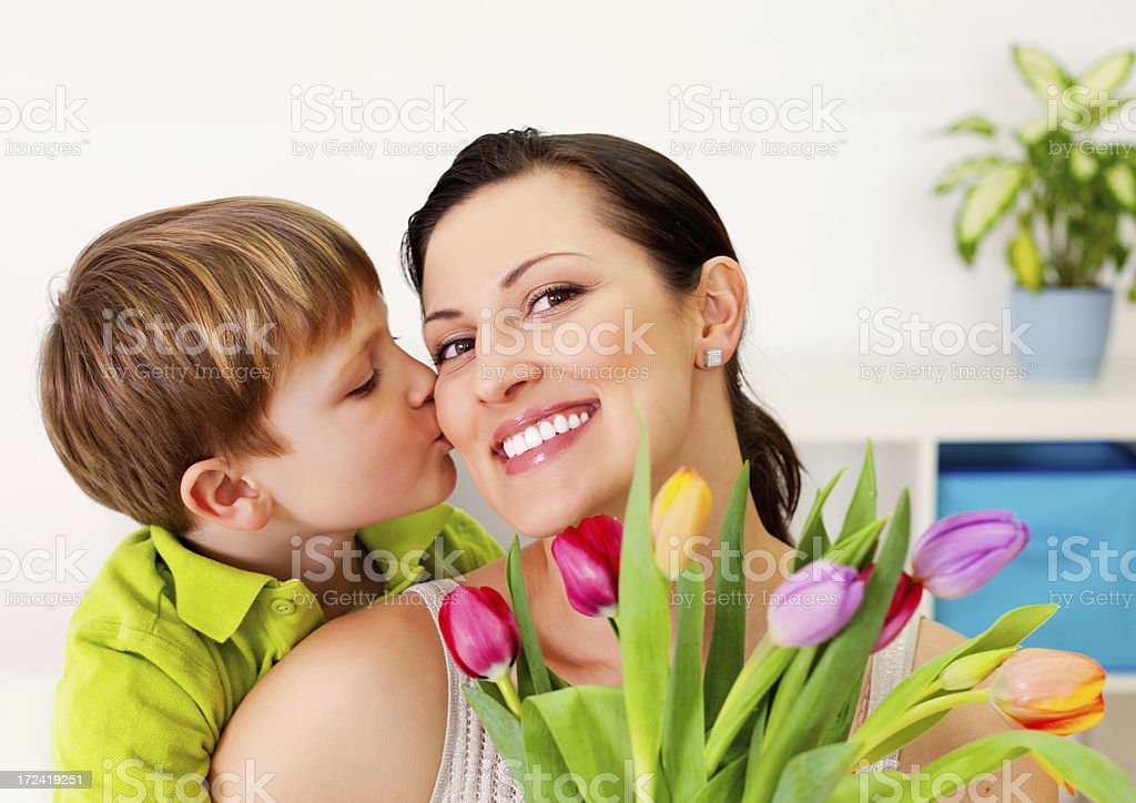 Picture of boy kissing mom and giving her flowers royalty-free stock photo
