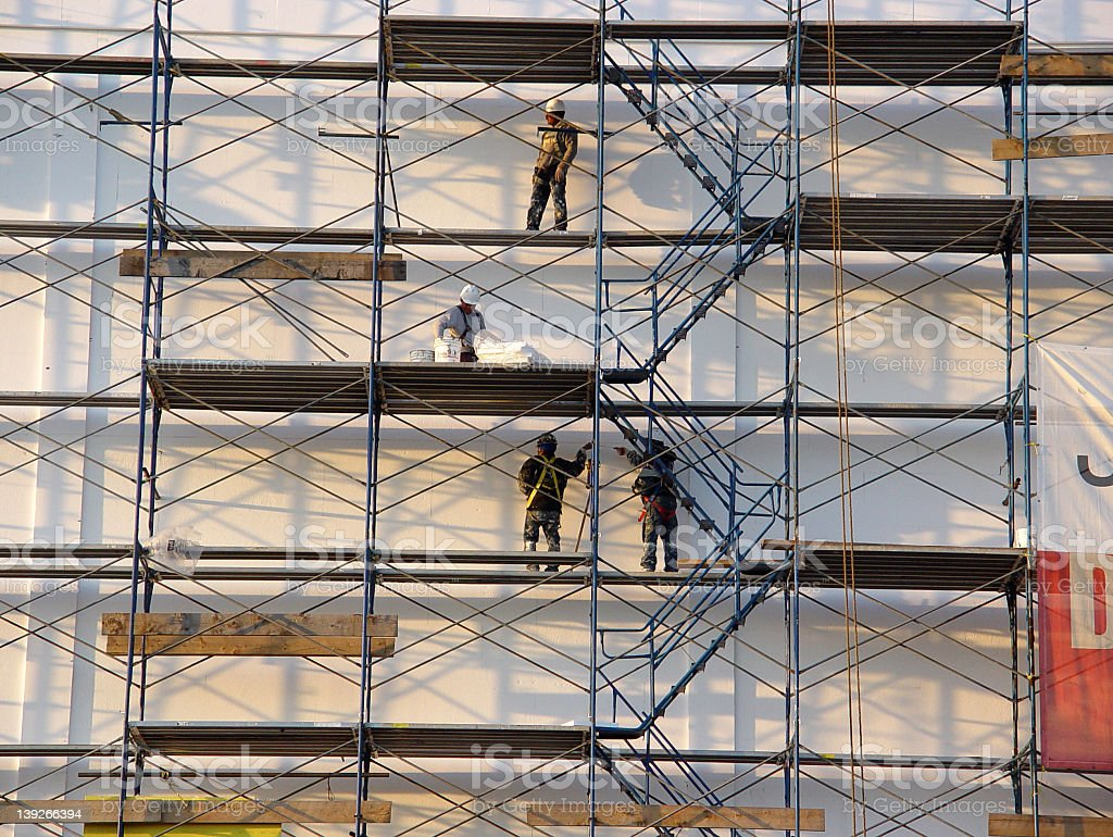 Picture of four men working on a scaffolding  stock photo