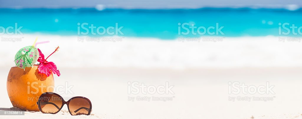 picture of fresh coconut juice and sunglasses on tropical beach stock photo
