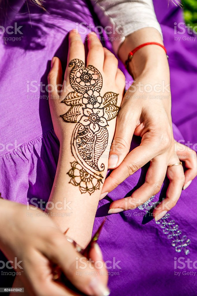 Picture of human hand being decorated with henna tattoo, mehendi stock photo