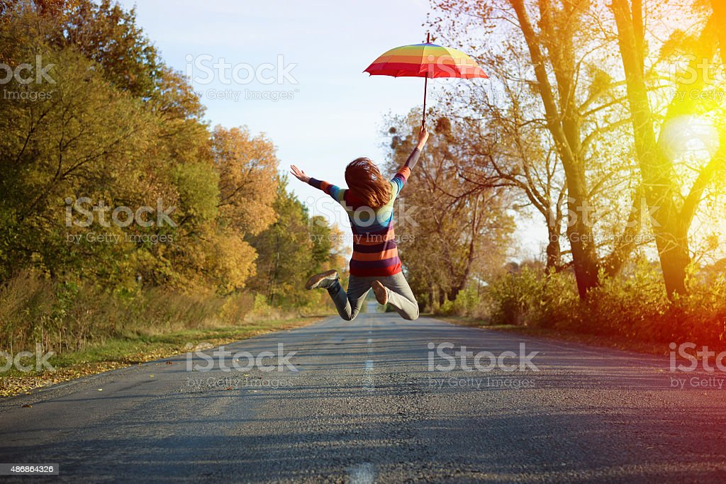Picture of jumping lady holding umbrella with arms sideways stock photo