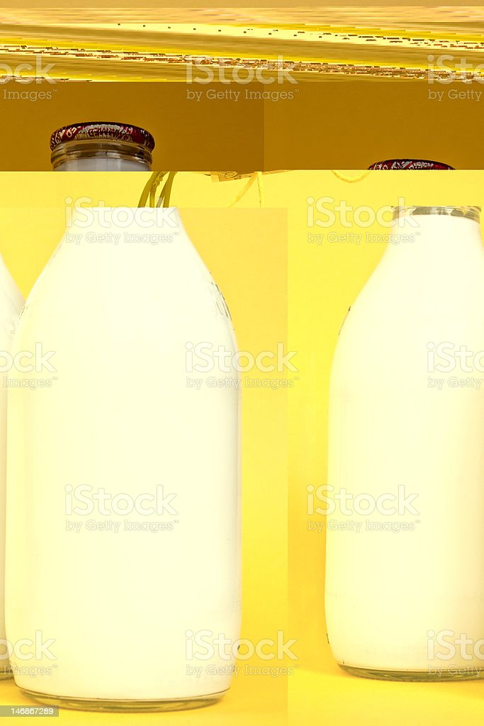 A picture of milk bottles on a yellow counter royalty-free stock photo