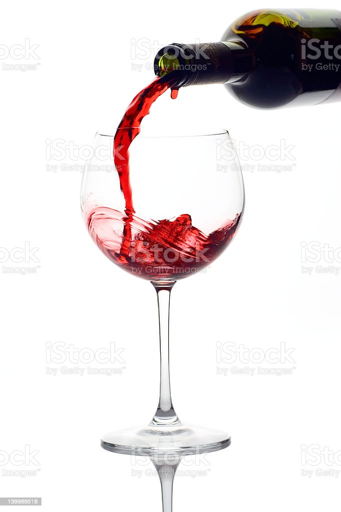 A picture of red wine being poured in a glass cup stock photo