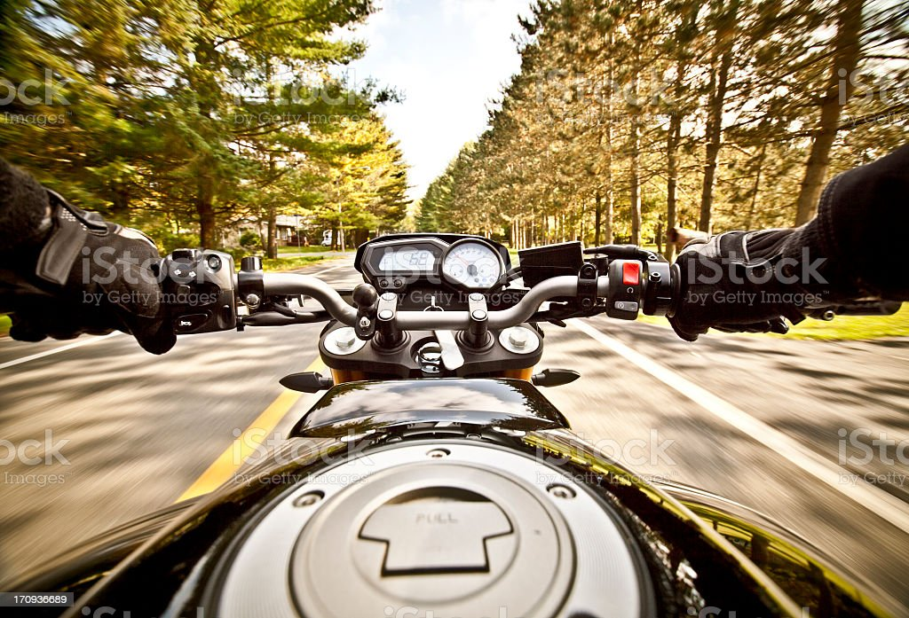 Picture of rider in motorcycle on road with trees stock photo