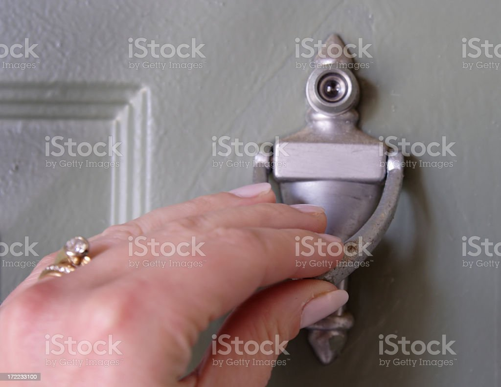 A picture of someone using a door knocker stock photo