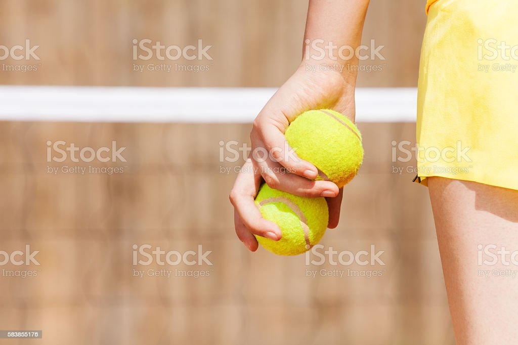 Close-up picture of female tennis player\'s hand, holding two tennis...