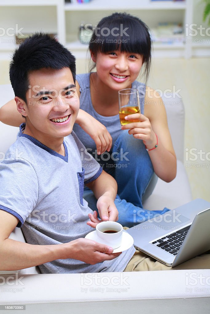 picture of young asian couple in couch with laptop royalty-free stock photo