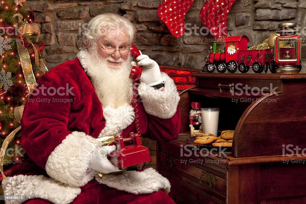Pictures of Real Santa Claus Talking on Red Vintage Telephone royalty-free stock photo