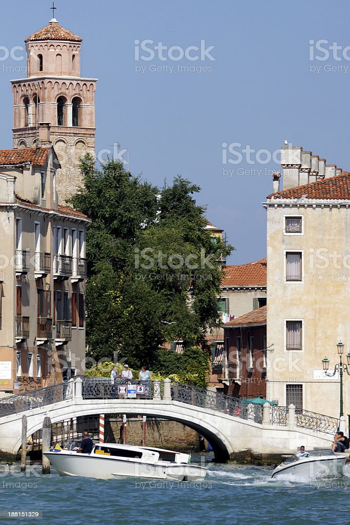 picturesque canals with motor boats and bridge in Venice, Italy royalty-free stock photo
