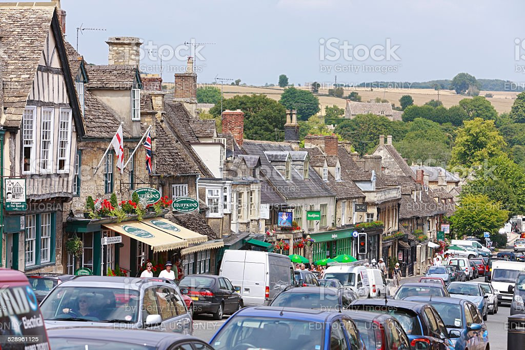 Picturesque Cotswolds village high street with traffic stock photo