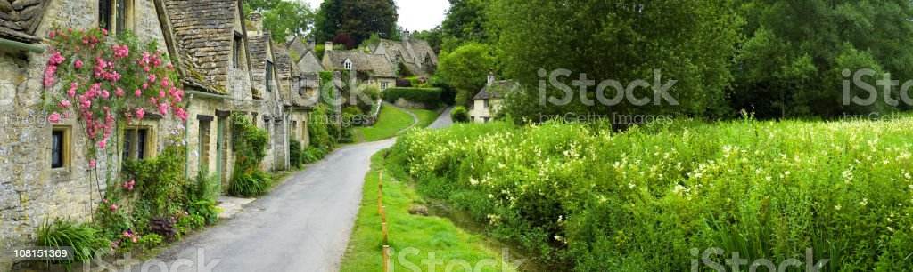 Picturesque English cottages water meadow Cotswold village panorama Arlington Row stock photo