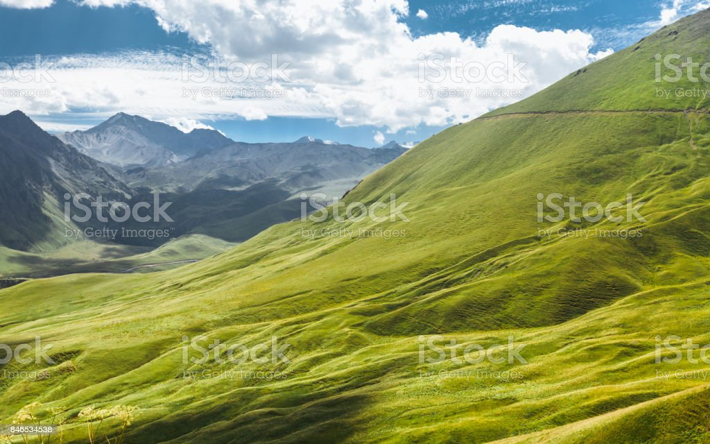 Picturesque Mountain Landscape. Green Hill And Mountain Range On A Sunny Summer Day. Elbrus Region, North Caucasus, Russia stock photo