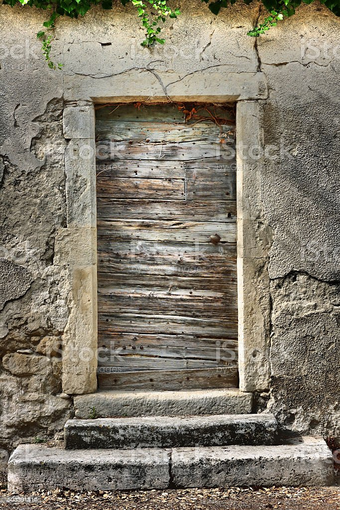 Picturesque Provence: Old weathered wooden door in the village Grignan stock photo