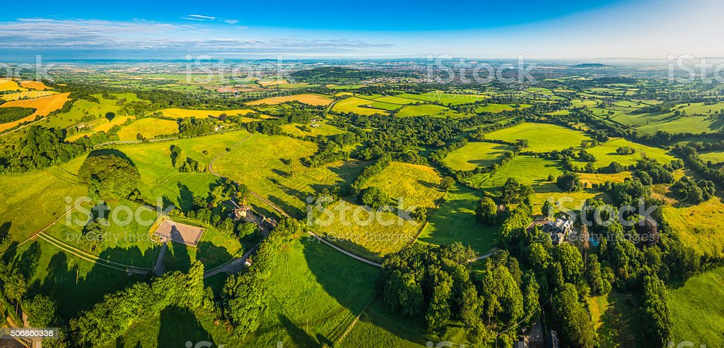 Picturesque rural landscape patchwork fields farms country village aerial panorama stock photo