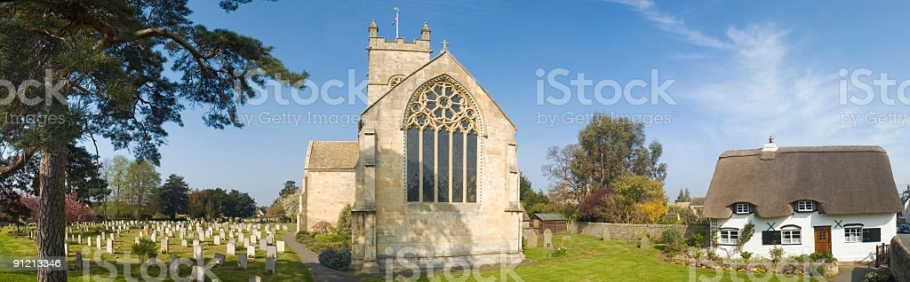 Picturesque thatched cottage and churchyard royalty-free stock photo
