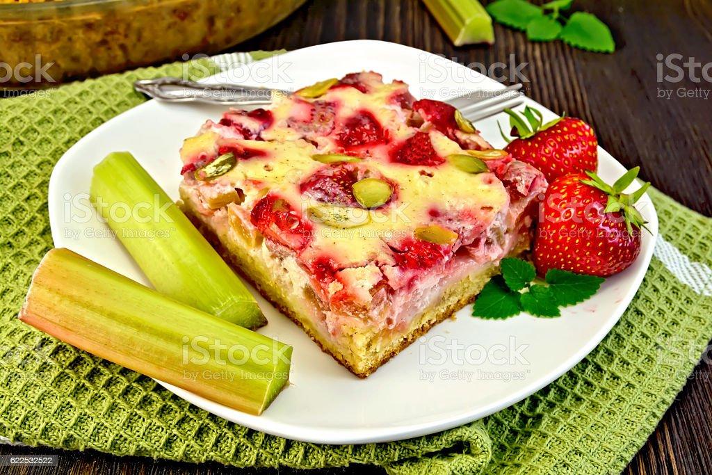 Pie strawberry-rhubarb with sour cream on green napkin stock photo