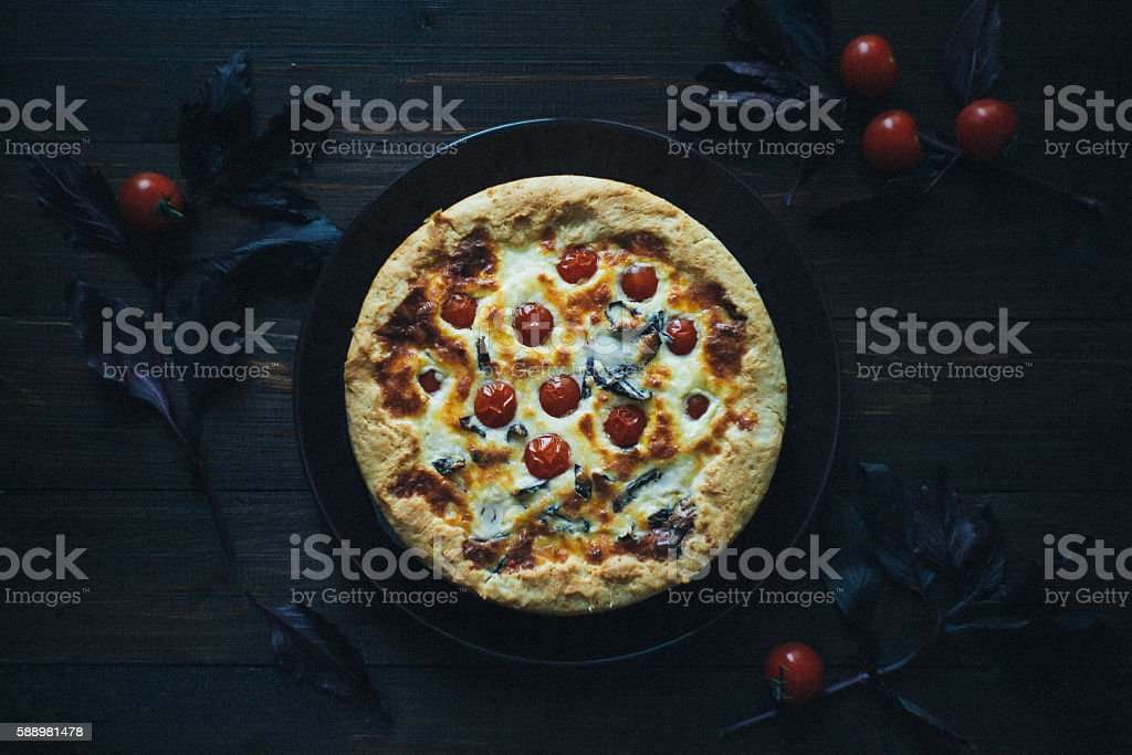 Pie with cheese, сherry tomatoes and basil stock photo