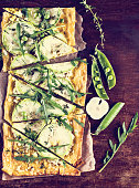 pie with zucchini, green peas, cheese and arugula