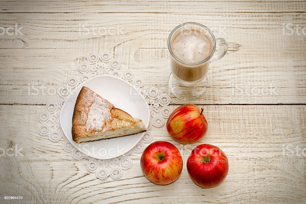 Piece of apple pie, cappuccino and ripe apples, wooden background stock photo