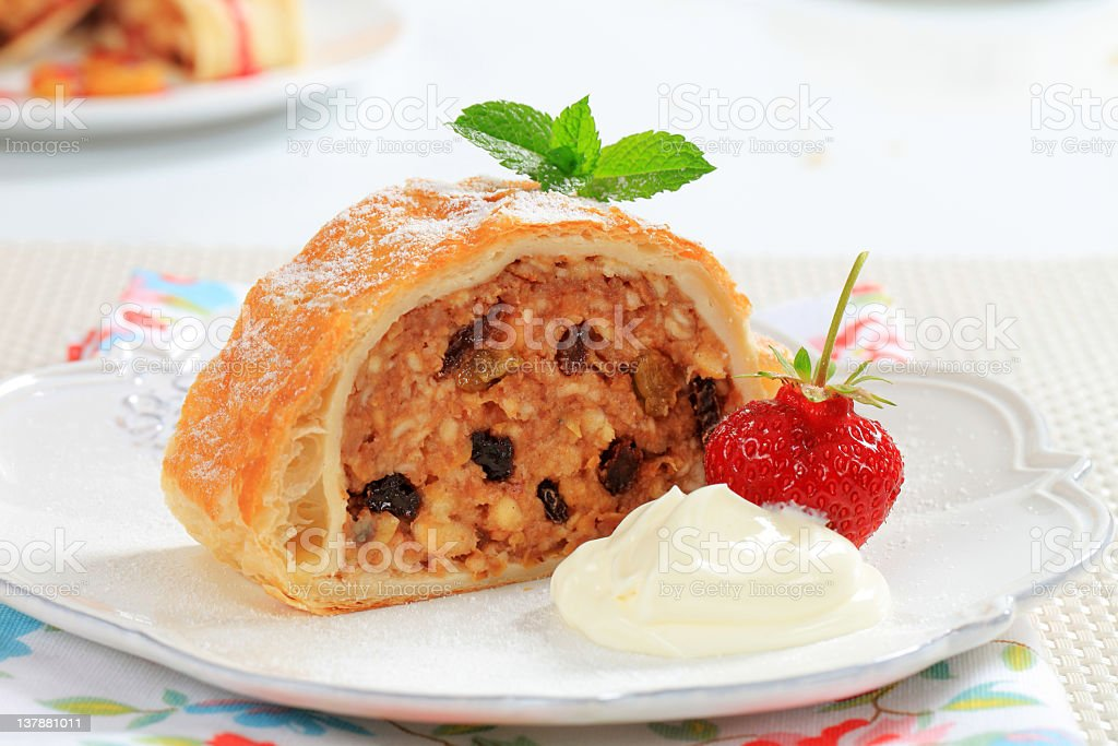 Piece of apple strudel on a plate, strawberry, whipped cream stock photo