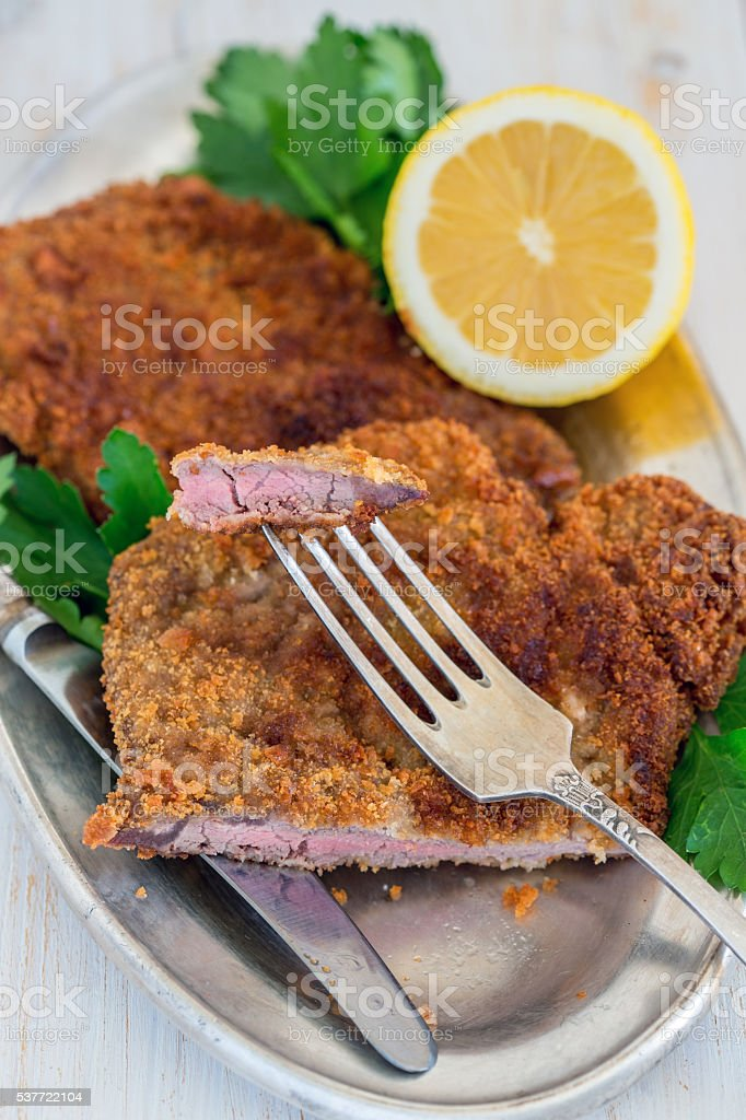 Piece of beef schnitzel on a fork. stock photo